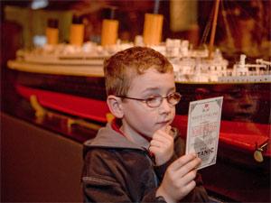 Garoto segura cartão de embarque de 'Titanic: a exposição' (Foto: Divulgação)