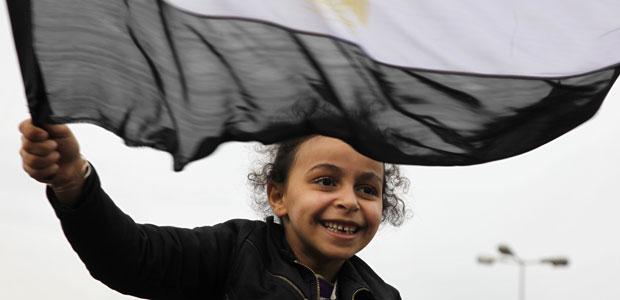Menina agita bandeira do Egito neste sábado (5) na Praça Tahrir (Foto: AP)