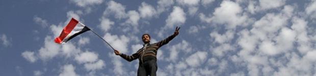 Manifestante acena bandeira do Egito na Praça Tahrir neste domingo (6) (Foto: AFP)