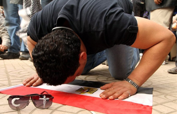 Egípcio ora prostrado sobre bandeira do país na Praça Tahrir, neste domingo (6); em seus óculos escuros, o crescente, símbolo do Islã, e a cruz, símbolo do cristianismo (Foto: Reuters)