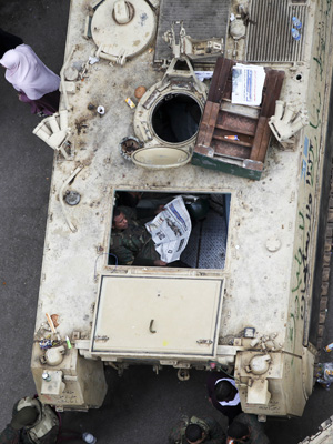 Soldado lê jornal dentro de veículo armado neste domingo (6) na Praça Tahrir, no Cairo (Foto: AP)