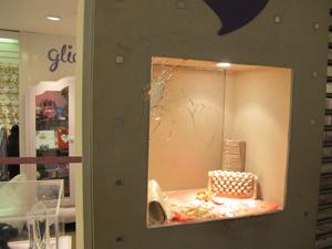 Loja teve vidraça quebrada após tiros (Foto: Marcelo Mora/G1)