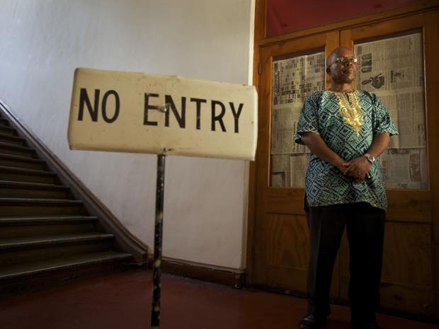 O diretor da National Gallery, Voti Thebe, posa em frente à entrada da exposição fechada; a janela de vidro foi encoberta por jornal controlado pelo Estado (Foto: Robin Hammond/The New York Times)