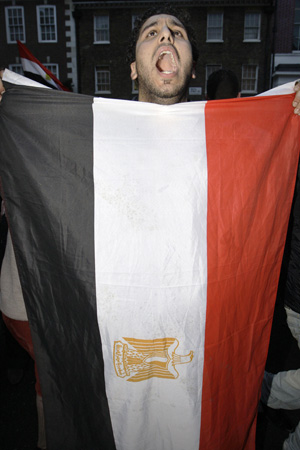 Egípcio, com bandeira do país, comemora o anúncio nesta sexta-feira (11) (Foto: AP)