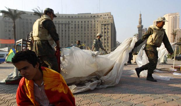 Manifestante antigoverno senta no chão da praça Tahrir, local símbolo dos protestos no Egito, enquanto militares removem barracas, neste domingo (13)  (Foto: Yannis Behrakis / Reuters)