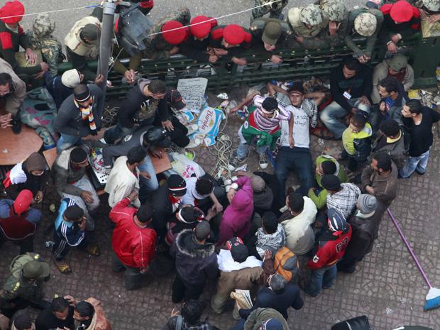 Manifestantes protestam ao lado de militares nesta segunda-feira (14) na Praça Tahrir, no Cairo (Foto: Reuters)