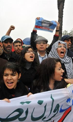 Marroquinos levantam suas mãos durante protesto em que pedem reformas políticas no governo do país (20/2) (Foto: AFP)