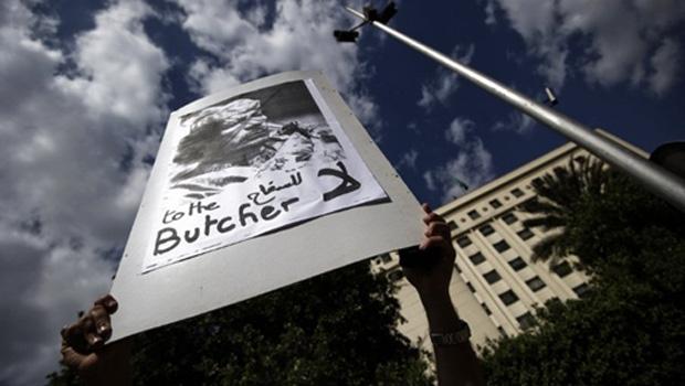 Manifestante mostra cartaz contrário ao presidente da Líbia, Muammar Kadhafi, durante protesto no Cairo, capital do Egito, nesta segunda-feira (21) (Foto: Reuters)