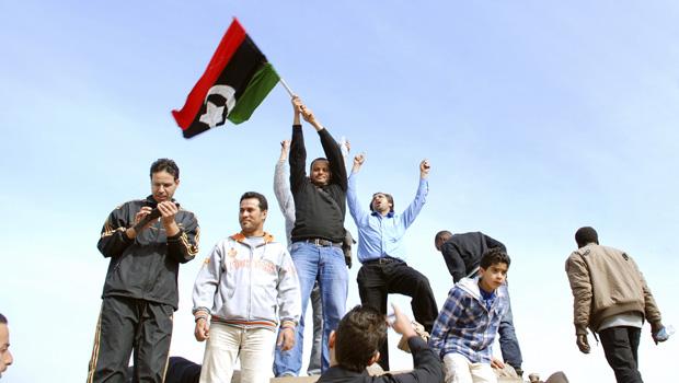 Moradores sobre tanque com a bandeira nacional pré-Kadhafi, nesta segunda-feira (21), na cidade líbia de Benghazi. (Foto: AP)