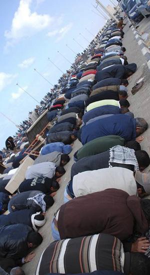 Manifestantes oram durante protestos em Benghazi; a foto, de data não confirmada, foi postada no Facebook por ativistas (Foto: Reuters)