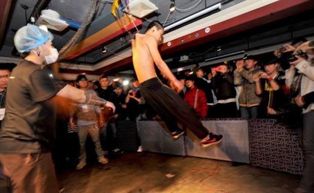 Homem fica suspenso por ganchos presos ao teto em bar chinês. (Foto: AFP)