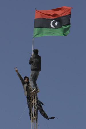 Manifestantes içam a antiga bandeira da Líbia, pré-Kadhafi, durante protesto nesta quarta-feira (23) em Tobruk (Foto: AP)