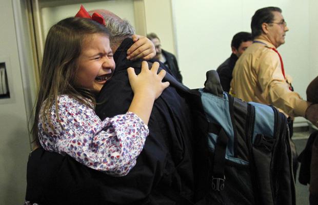 Menina espanhola identificada como Panchi encontra o pai em Madri nesta quarta-feira (23) após chegar de Trípoli. (Foto: Reuters)