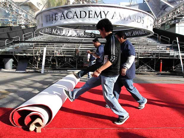 A instalação do tapete vermelho á parte dos últimos preparativos para a 83ª cerimônia de entrega do Oscar. Anne Hathaway e James Franco serão os apresentadores da festa, que tem como favorito o filme 'O discurso do rei', com 12 indicações (Foto: AP)