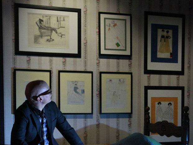 Um funcionário da galeria Truman Brewery, em Londres, posa ao lado de alguns trabalhos de Freddie Mercury, na exposição sobre o líder do Queen. (Foto: Reuters)