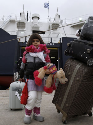 Criança desembarca de navio com brasileiros que chegou em Atenas, na Grécia (Foto: John Kolesidis / Reuters)