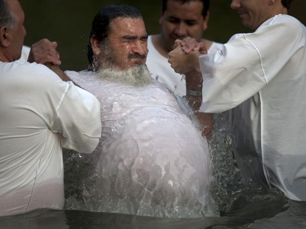 Um dos 33 mineiros resgatados no ano passado na Mina San  José, no Chile, é batizado nesta segunda-feira (28) no Rio Jordão, onde,  segundo a tradição cristã, Jesus Cristo foi batizado. Os mineiros, que  viraram celebridade depois do resgate, estão em uma v (Foto: AP)
