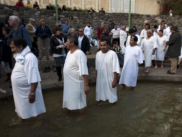 Alguns dos 33 mineiros resgatados no ano passado na Mina San  José, no Chile, fazem fila para serem batizados nesta segunda-feira (28)  no Rio Jordão, onde, segundo a tradição cristã, Jesus Cristo foi  batizado. (Foto: AP)