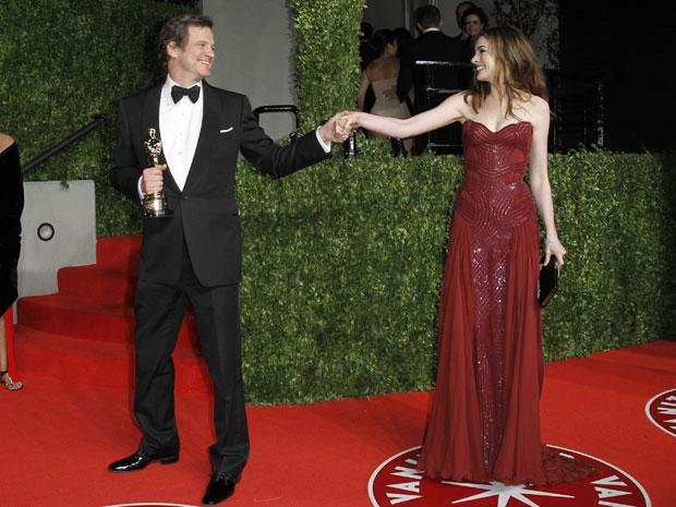 O ator Colin Firth posa com sua estatueta de melhor ator junto à atriz Anne Hathaway na festa da 'Vanity Fair' (Foto: Reuters)