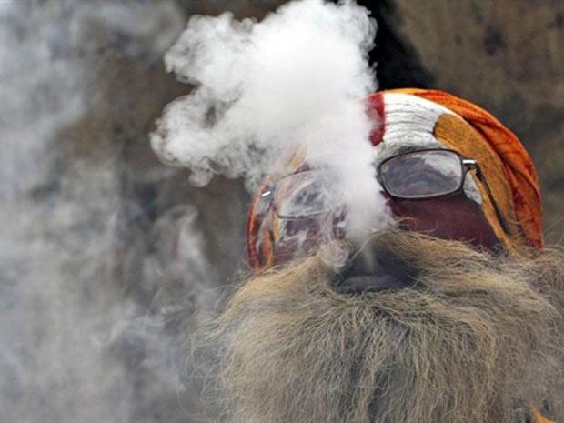 Sadhu (homem sagrado indu) fuma maconha em cachimbo de argila como oferenda para o deus Shiva, no templo Pashupatinath, em comemoração ao festival Maha Shivaratri, em  Kathmandu (Foto: Prakash Mathema/AFP)