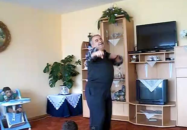 Homem dança observado por duas crianças. (Foto: Reprodução)