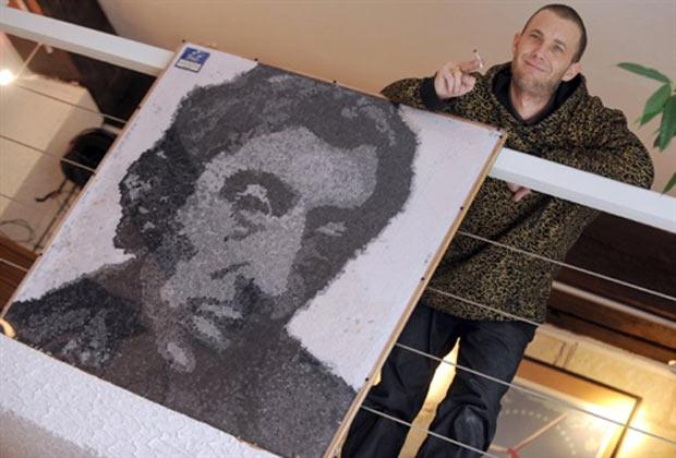 Kunst Stencil posa ao lado de retrato de Serge Gainsbourg feito com filtros de cigarros. (Foto: Frank Perry/AFP)