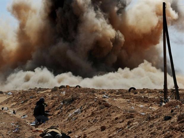 Rebeldes protegem-se durante bombardeio à região próxima a Ras Lanuf nesta segunda-feira (7) na Líbia (Foto: AFP)
