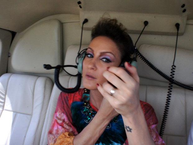 Claudia Leitte retoca maquiagem em pleno voo de helicóptero (Foto: Glauco Araújo/G1)