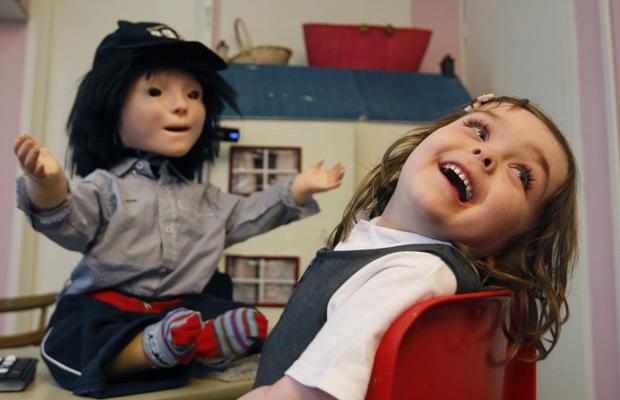 A garota Eden Sawczenko brinca com o robô Kasper, durante pesquisa em Hatfield, na Inglaterra. O robô está sendo usado para ajudar crianças autistas em uma creche em Stevenage, em sessões semanais. As crianças brincam com o robô, controlado remotamente pelos cientistas por cerca de 10 minutos. (Foto: AP)