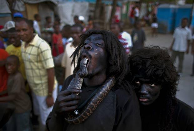 Homem foi flagrado no domingo (6) colocando uma cobra na boca durante as comemorações do carnaval em Port-au-Prince, no Haiti. (Foto: Ramon Espinosa/AP)