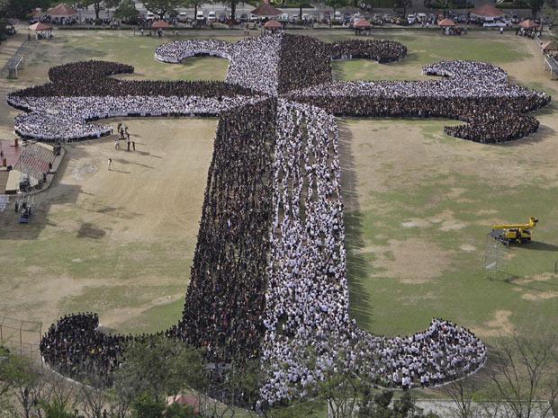 estudantes, funcionáros e seminaristas da Universidade de Santo Tomas se juntam para formar uma cruz gigante em Manila, nas Filipinas. Segundo os organizadores, a cruz reuniu mais de 20 mil pessoas, numa tentativa de entrar para o Livro dos Recordes com a 'maior cruz humana' (Foto: Aaron Favila/AP)