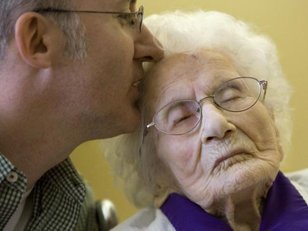 A americana Besse Cooper, de 114 anos, recebe um beijo de seu neto Paul Cooper, 42, nesta quinta-feira (10), na cerimônia em que ela foi reconhecida pelo Livro Guinness de Recordes como a mais velha pessoa viva. A cerimônia ocorreu na casa de repouso em q (Foto: AP)