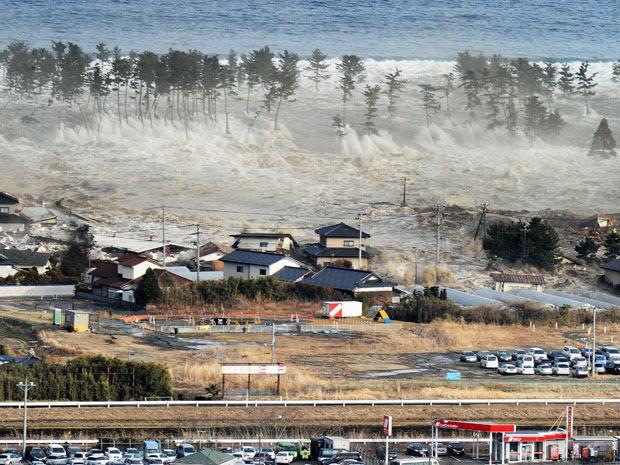 Ondas do tsunami atingem casas em Natori (Foto: AP)