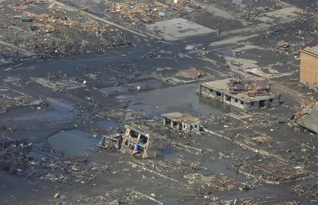 Imagem aérea mostra casas cobertas por lama na cidade portuária de Rikuzentakata neste sábado (12) (Foto: AP)