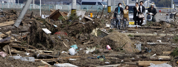 Moradores passam por destroços em Sendai, na província de Miyagi, neste domingo (13) (Foto: AP)