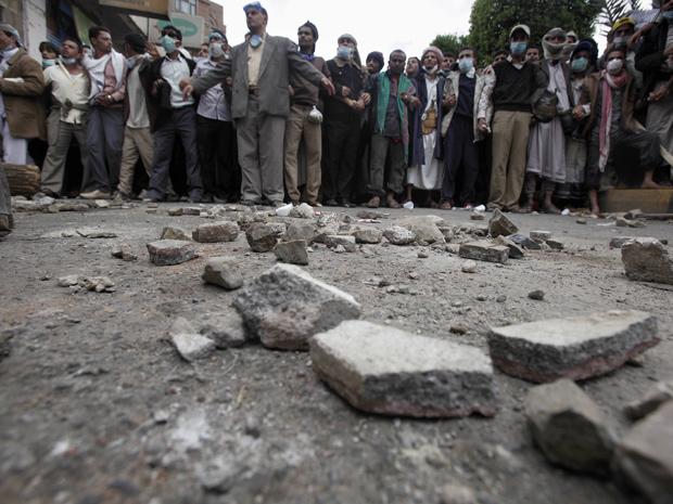 Manifestantes durante confronto com a polícia neste domingo (13) em Sanaa, capital do Iêmen (Foto: AP)