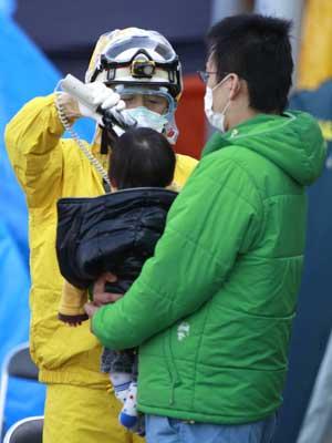 Equipe médica analisa se homem e criança retiradas da região da usina nuclear de Fukushima estão contaminados por radiação. (Foto: Wally Santana / AP Photo)