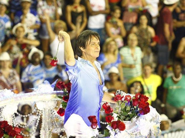 Roberto Carlos joga flor do alto do carro alegórico durante o desfile das campeãs (Foto: Rodrigo Gorosito/G1)