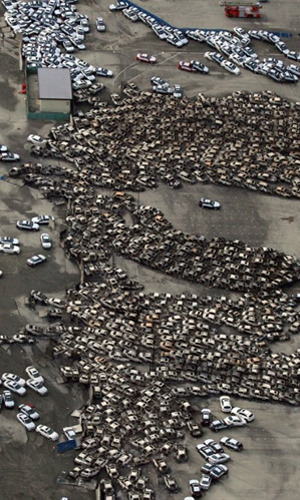 Carros destruídos em Sendai vistos em imagem aérea nesta segunda-feira (14) (Foto: AFP)