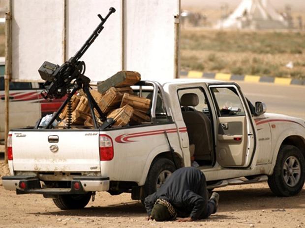 Rebelde ora ao lado de veículo armado na cidade líbia de Ajdabiya nesta segunda-feira (14) (Foto: Reuters)