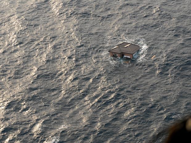 Foto divulgada nesta segunda-feira (14) pela Marinha dos EUA mostra casa devastada pelo tsunami à deriva no Oceano Pacífico. A foto foi tomada no domingo, dois dias após o tsunami. Navios e aeronaves americanos procuram sobreviventes nas regiões costeiras (Foto: AP)