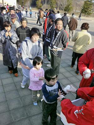 Deslocados da região próxima à usina nuclear em risco recebem comida em Tamura, em Fukushima (Foto: AP)