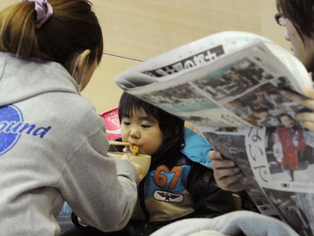 Criança come em abrigo em Tamura (Foto: AP)