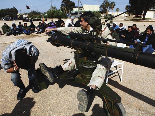 Rebeldes líbios ensinam voluntários a usar armamento em Benghazi, nesta segunda (14) (Foto: Finbarr O'Reilly / Reuters)