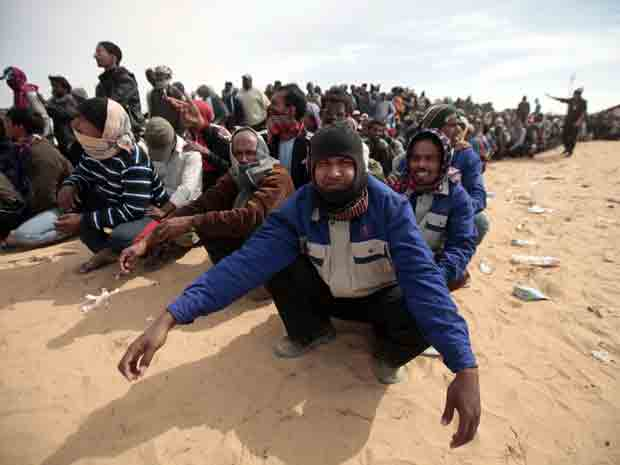 Homem espera por comida em campo de refugiado na fronteira da Líbia com Tunísia (Foto: AP)