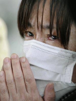 Mulher lamenta ao receber a notícia da morte de parente vítima do tsunami e do terremoto, nesta terça-feira (15), em Kesennuma, no distrito de Miyagi, no Japão. (Foto: AP/Kyodo News)