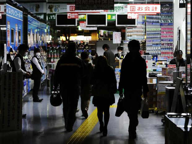 Loja funciona parcialmente às escuras para economizar energia elétrica nesta terça-feira (15) em Tóquio, capital do Japão (Foto: AP)