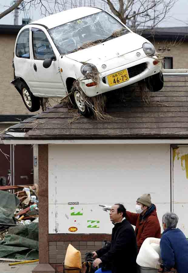 Carro para em telhado de casa em Sendai, uma das mais devastadas pelo tsunami que atingiu o Japão na última sexta-feira (11) (Foto: Reuters)