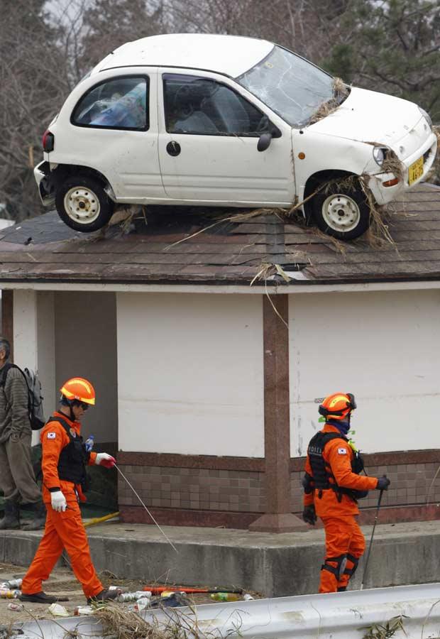 Carro para no telhado de casa por causa de tsunami. Bombeiros trabalham na região (Foto: Reuters)