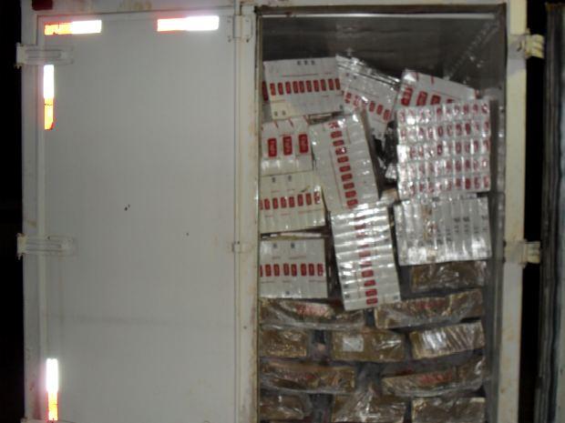 A Polícia Rodoviária Estadual (PRE-PR) apreendeu um caminhão com 3.500 maços de cigarro na PR-328, próximo a Iporã, região Noroeste do Paraná, por volta das 1h desta terça-feira (15). O veículo, que tinha placas de Cascavel (PR), também levava uma carga de carnes, para disfarçar o contrabando. Segundo o motorista, o caminhão seria levado até São Paulo. O motorista, o caminhão e a mercadoria foram encaminhados à Delegacia da Polícia Federal de Guaíra (PR).  (Foto: Divulgação/PRE-PR)